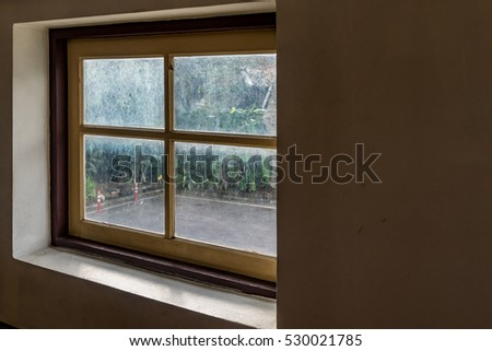 Glass window with wooden frame on concrete wall