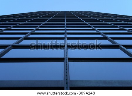 Glass-windowed skyscraper reaching the sky. View directly from below.