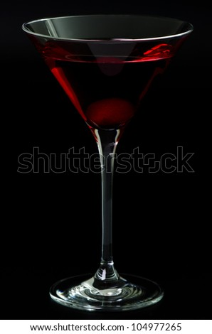 Glass with a red cocktail on a black background - stock photo