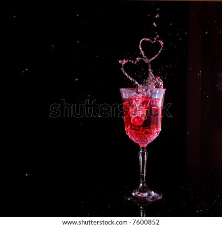 Glass with a splash shaped like hearts. - stock photo