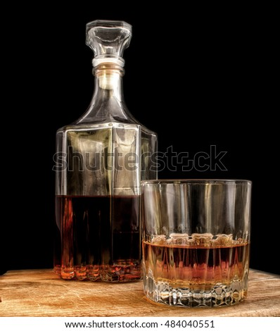 Glass with alcohol and a decanter on a black background.