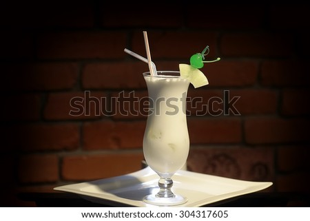 Glass with alcoholic pina colada cocktail of light rum coir coconut milk crushed ice frappe pineapple juice and slice green cherry and drink straws on white plate on brick background, horizontal photo - stock photo