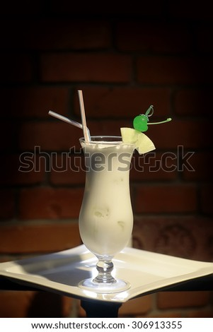 Glass with alcoholic pina colada cocktail of light rum coir coconut milk crushed ice frappe pineapple juice and slice green cherry and drink straws on white plate on brick background, vertical photo - stock photo