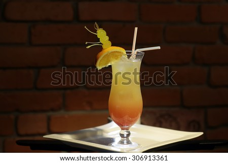 Glass with alcoholic sex on beach cocktail of vodka peach liqueur cranberry water orange juice and slice with green grapes and drink straws on white plate on brick wall background, horizontal photo - stock photo