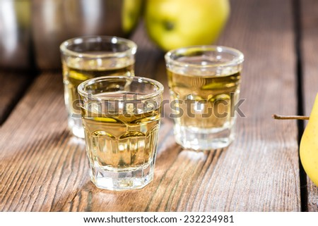 Glass with Apple Liqueur on dark vintage wooden background