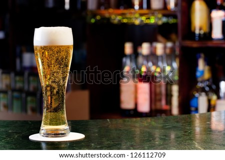 glass with beer on the background of the bar - stock photo