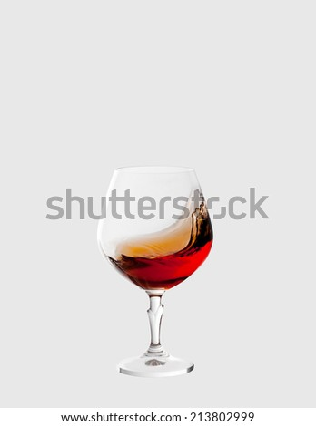 glass with brandy and splashes isolated on light grey background - stock photo