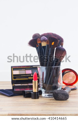 glass  with  brushes and make up products on wooden table with copy space