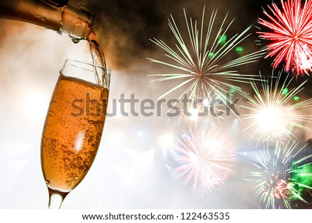 Glass with champagne against fireworks - stock photo