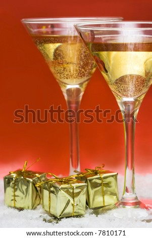 glass with champagne and gift boxes - stock photo