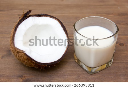Glass with coconut milk on wooden table - stock photo