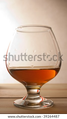 glass with cognac and bottle - stock photo