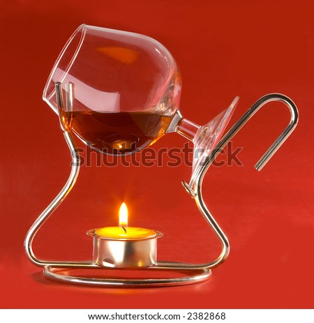 glass with cognac and candles - stock photo