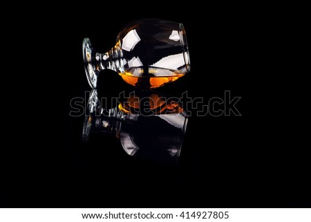 glass with cognac on a black background - stock photo