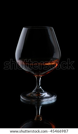 Glass with cognac on a black background. - stock photo