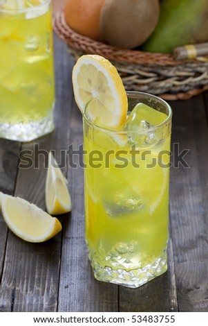 Glass with cold lemon beverage on wooden table top - stock photo