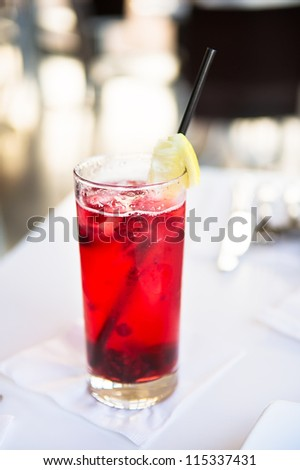 Glass with cranberry cocktail with lemon on the top