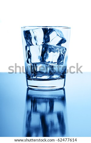 Glass with crystal clear ice cubes on glossy background - stock photo