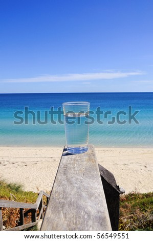 glass with crystal clear water against the blue ocean - as a symbol of purity, freedom and health.