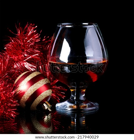 Glass with drink, a Christmas ball and tinsel on a black background. Glass with alcohol and a Christmas ball. - stock photo