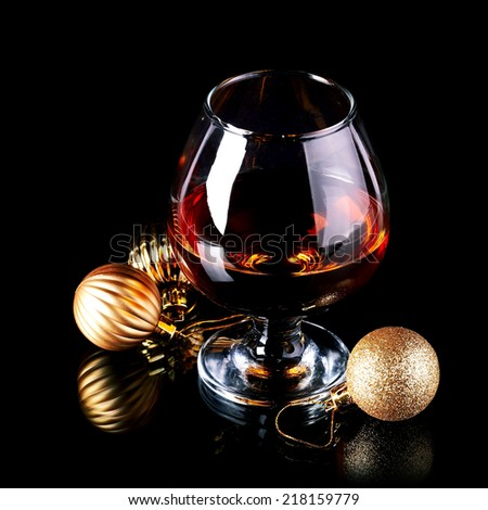 Glass with drink and a Christmas balls on a black background. New Year's balls and glass. Glass with alcohol and a Christmas ball. - stock photo