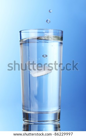 Glass with efervescent tablet in water on blue background