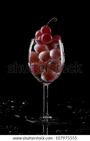 Glass with grape on black with reflection - stock photo