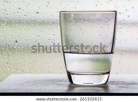Glass with half a glass of water scenes with condensation glass. - stock photo