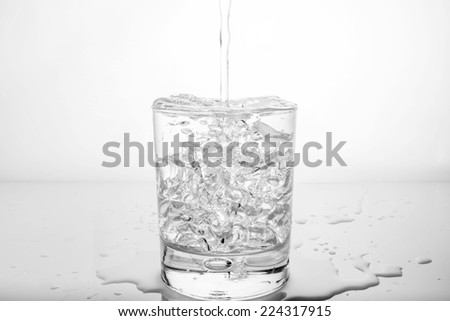 glass with ice and splashing water  - stock photo