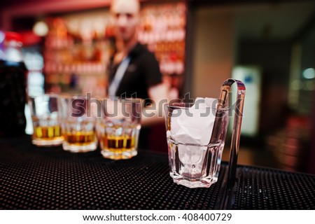 Glass with ice and tongs with three whiskey glasses background barman - stock photo