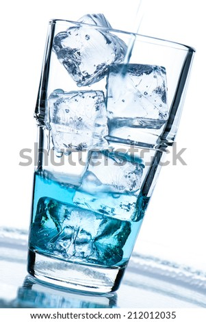 Glass with ice cubes and blue drink in vertical format
