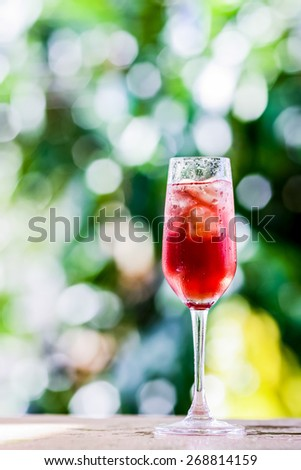 glass with ice cubes and grape flavored beverage background blurring of trees in a park. The purpose of this blur effect to indicate freshness, organic and natural environment.  - stock photo