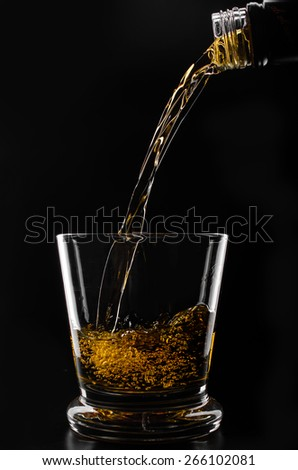 glass with ice in which pour whiskey on a black background - stock photo