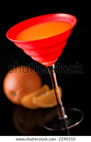 Glass with juice and oranges on black, focus on glass - stock photo