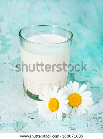 glass with milk and camomiles a shabby wooden background - stock photo