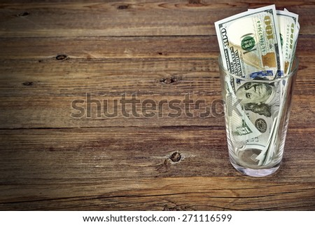 Glass  With Money  for Big Tip Or Savings With Dollar Bills On Rough Wood Background - stock photo