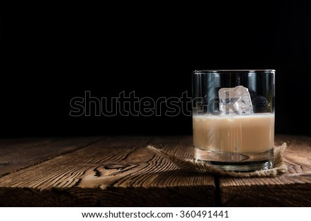 Glass with original Irish Cream Liqueuron wooden background - stock photo