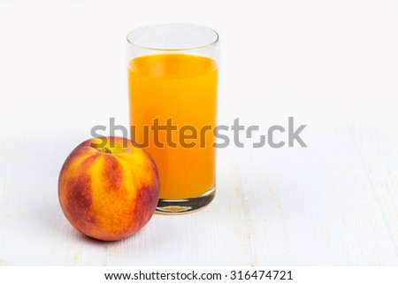Glass with peach juice and ripe peache on white wooden background