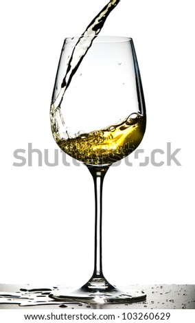 Glass with pouring white wine on a white background