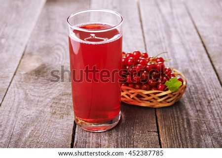glass with red currant drink  and currant berries on wooden table