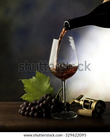 Glass with red wine and grapes on the wooden table