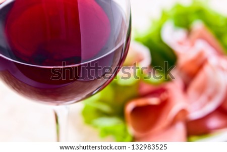 glass with red wine and ham with salad , focus on a foreground - stock photo
