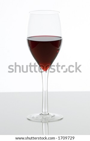 Glass with red wine on a glass table isolate on white background