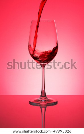 Glass with red wine on a red background - stock photo