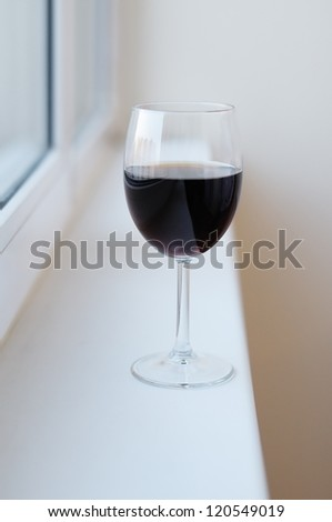 Glass with red wine on the windowsill - stock photo