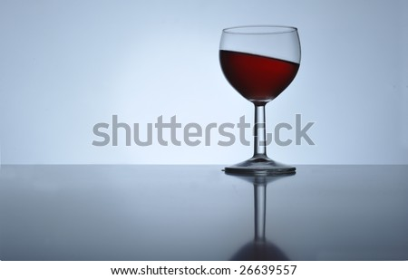Glass with red wine standing oblique, close up