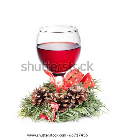 Glass with red wine surrounded by christmas decoration made of pine branch with cones