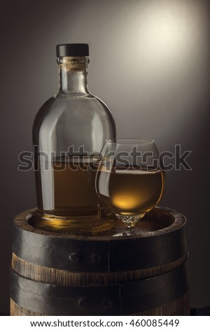 Glass with rum and bottle on old wooden barrel
