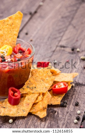 Glass with Salsa Sauce and Nachos on wooden background - stock photo