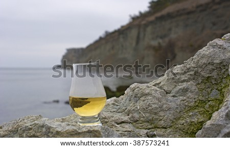 Glass with single malt whiskey standing on a limestone rock with ocean in the background - stock photo